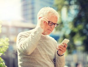 Senior Cell Phone Addiction: senior man texting message on smartphone in city