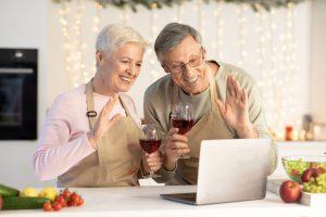 virtual New Year's Eve - Senior couple celebrating party with wine