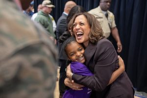 Kamala Harris, first female vice president, hugs a young girl