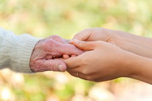 Importance of physical touch in seniors - old and young hand touching